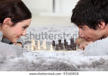 Man and woman playing chess - stock photo