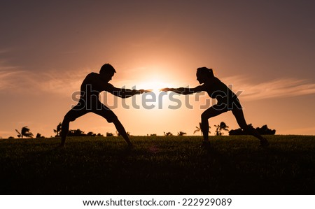Man and woman playing tug of war in the park - stock photo