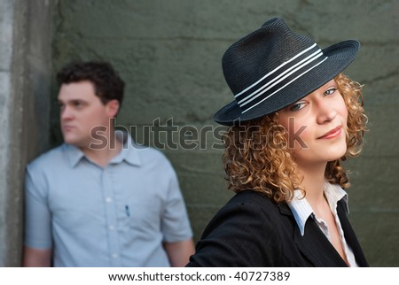 Man and woman posing  against concrete wall