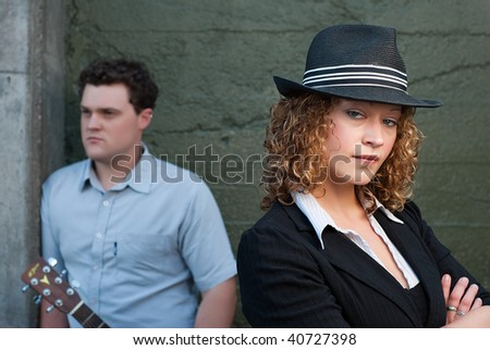 Man and woman posing  against concrete wall - stock photo