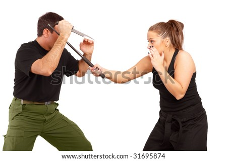 Man and woman practice fight using knife and truncheon - stock photo