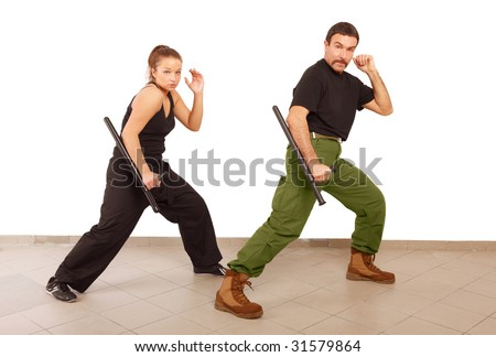 Man and woman practice fight with truncheon - stock photo