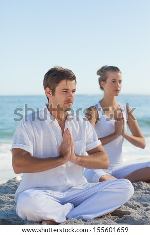 Man and woman practicing yoga on the beach on a sunny day - stock photo