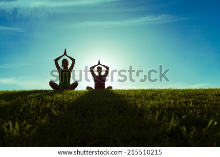 Man and woman practicing yoga outdoors. - stock photo