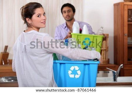 Man and woman preparing to recycle plastic bottles - stock photo