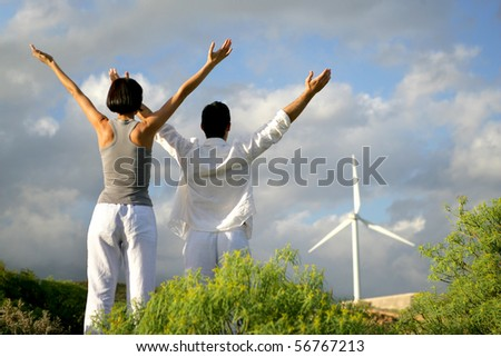 Man and woman raisin arms in front of wind turbines