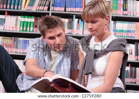 man and woman reading book in the library - stock photo