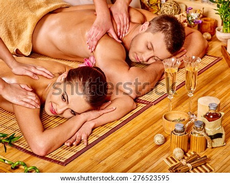 Man and woman relaxing in bamboo spa. Two  glass of champagne. - stock photo