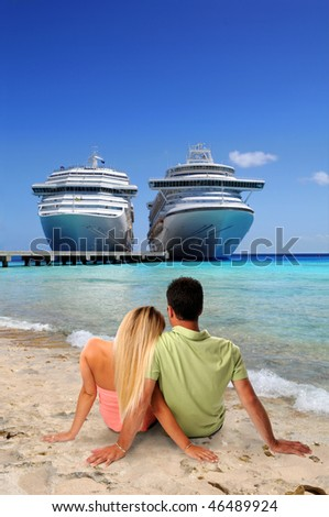 Man and Woman relaxing on beach with cruise ships in background - stock photo