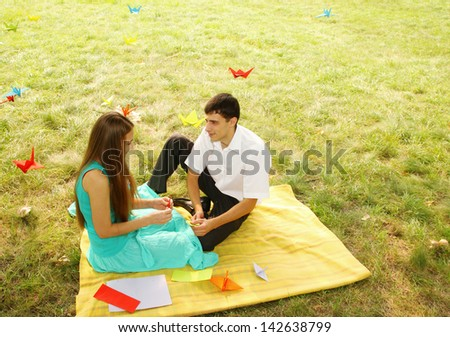 man and woman relaxing on nature make origami - stock photo
