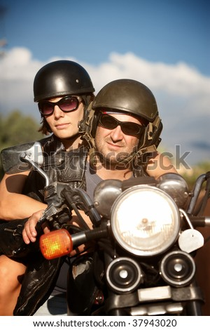 Man and Woman riding motorcycle against Blue Sky - stock photo