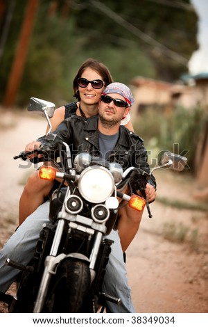 Man and Woman riding on vintage motorcycle - stock photo