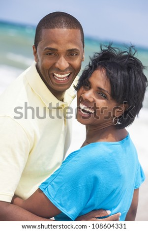 Man and woman romantic couple in embracing on a deserted tropical beach with bright clear blue sky - stock photo