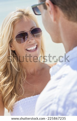 Man and woman romantic couple in white clothes on a deserted tropical beach wearing sunglasses - stock photo