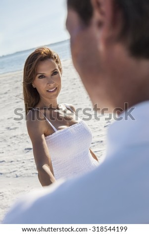 Man and woman romantic couple in white clothes walking or dancing on a deserted tropical beach  - stock photo