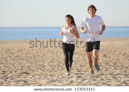 Man and woman running in the beach smiling - stock photo
