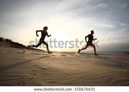 Man and woman running on beach at sunset
