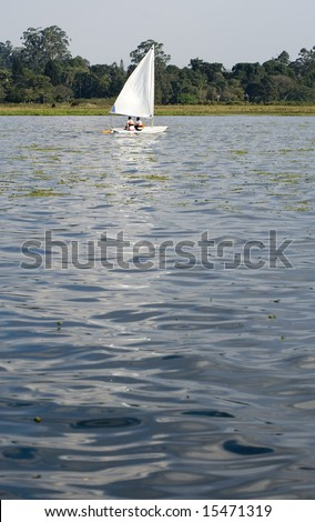 Man and woman sailing across lake. Photo from rear. Vertically framed photo. - stock photo