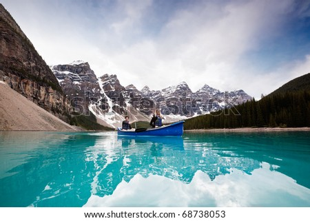 Man and woman sailing on peaceful lake against mountain range - stock photo