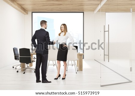Man and woman shaking hands in conference room with large square window; glass wall and a table with computers. Concept of board meeting. 3d rendering.