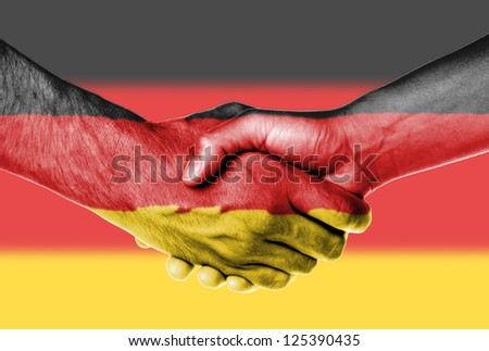 Man and woman shaking hands, wrapped in flag pattern, Germany - stock photo