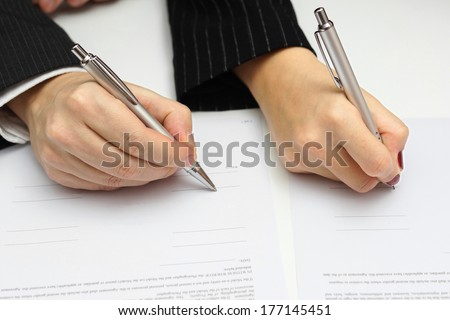 man and woman signing document or prenuptial agreement - stock photo