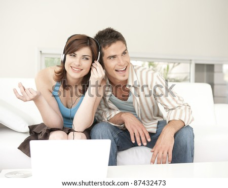 Man and woman singing to music at home, while using headphones and a laptop.