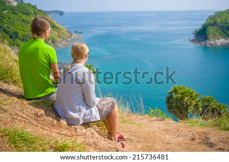 Man and woman sit and holding hands on tropical island cliff