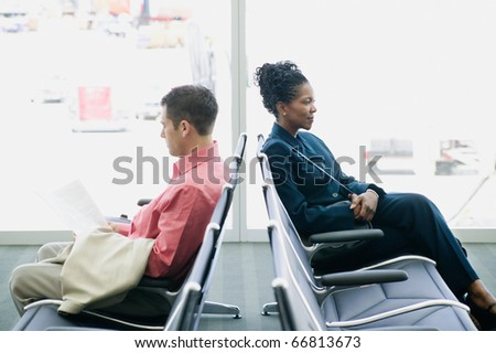 Man and woman sitting at airport - stock photo