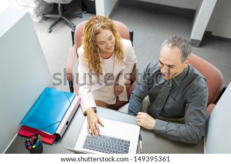 Man and woman sitting at desk with computer in office - stock photo
