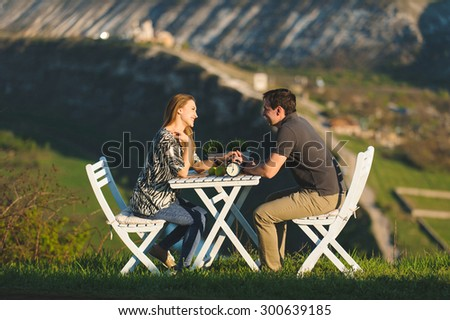 man and woman sitting at table on hill - stock photo