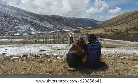 Man and woman sitting in snow moutain in Sechuan,China
