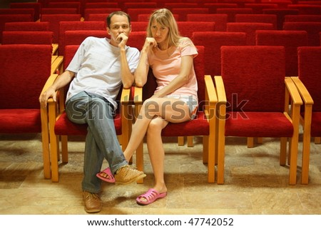 man and woman sitting on a chairs in empty presentation hall. - stock photo