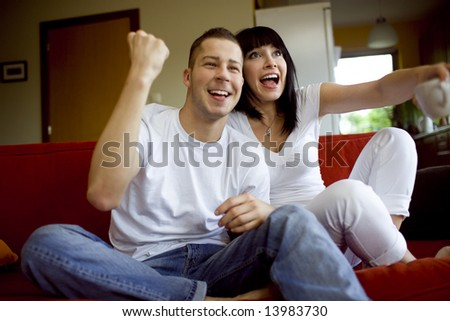 Man and woman sitting on a couch and watching tv - stock photo