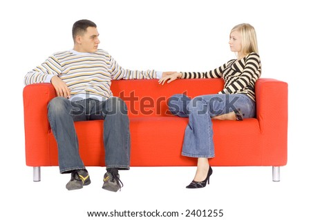 Man and woman sitting on a red couch looking their faces.  Isolated on white background, in studio.