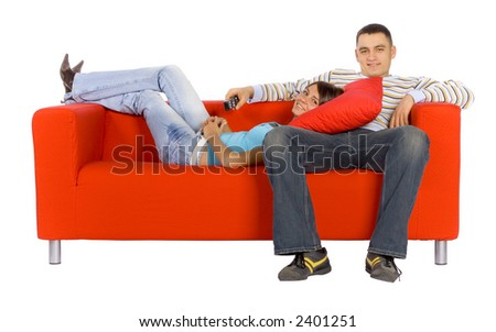 Man and woman sitting on a red couch with remote control.  Isolated on white background, in studio. - stock photo