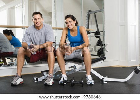 Man and woman sitting on exercise machine talking holding water bottles. - stock photo