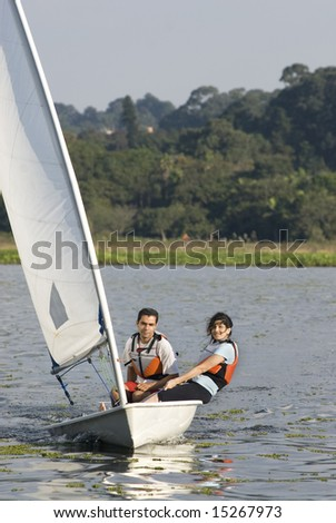 Man and woman sitting on sailboat leaning out over water and smiling at camera. Sailing across lake. Vertically framed photo - stock photo
