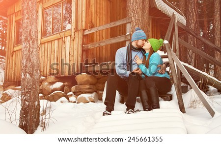man and woman sitting on the porch of a house. young happy couple in love outdoors in the winter - stock photo