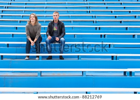 Man and woman sitting together on empty sports tribune along - stock photo