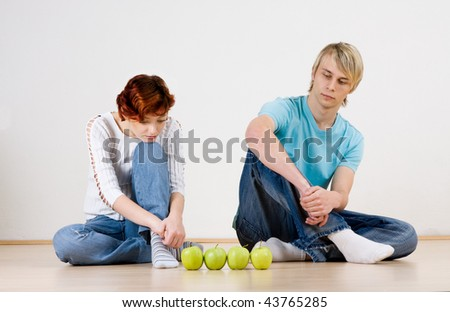 Man and woman sitting with four apples.