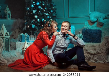 Man and woman smile at each other. They are a family on Christmas Eve. Under the Christmas tree decoration balls lie gifts. - stock photo