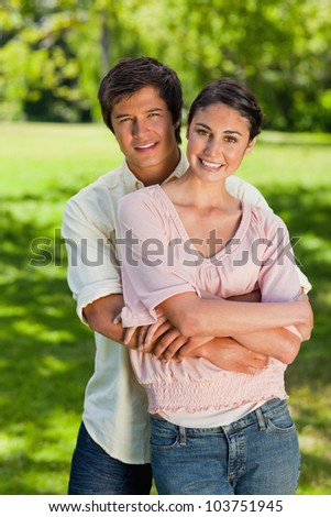 Man and woman smiling as he has his arms around her abdomen in a park