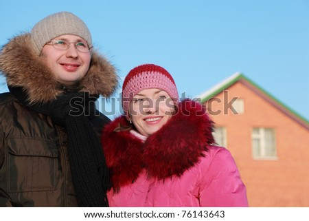 man and woman smiling in winter outdoors, house, red brick, blue sky - stock photo