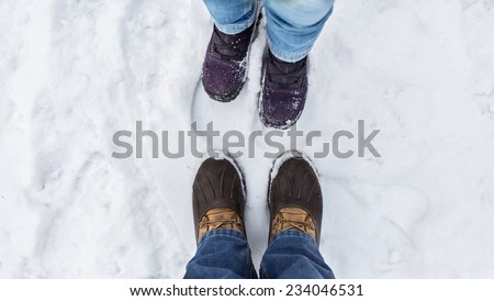 Man and woman stand opposite each other. Close up of feet in winter boots in the snow - stock photo
