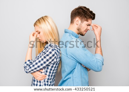 Man and woman standing back to back after quarrel - stock photo