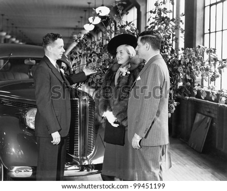 Man and woman standing in a car showroom talking to a salesman - stock photo