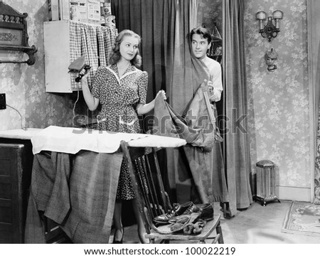 Man and woman standing in a kitchen while she is ironing his pants and he is behind a curtain - stock photo