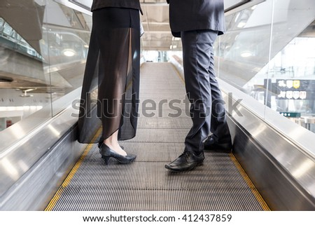 Man and Woman Standing in Moving Walkway