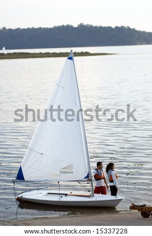 Man and woman standing in water next to sailboat. Couple launching sailboat. Staring across water. Vertically framed photo - stock photo